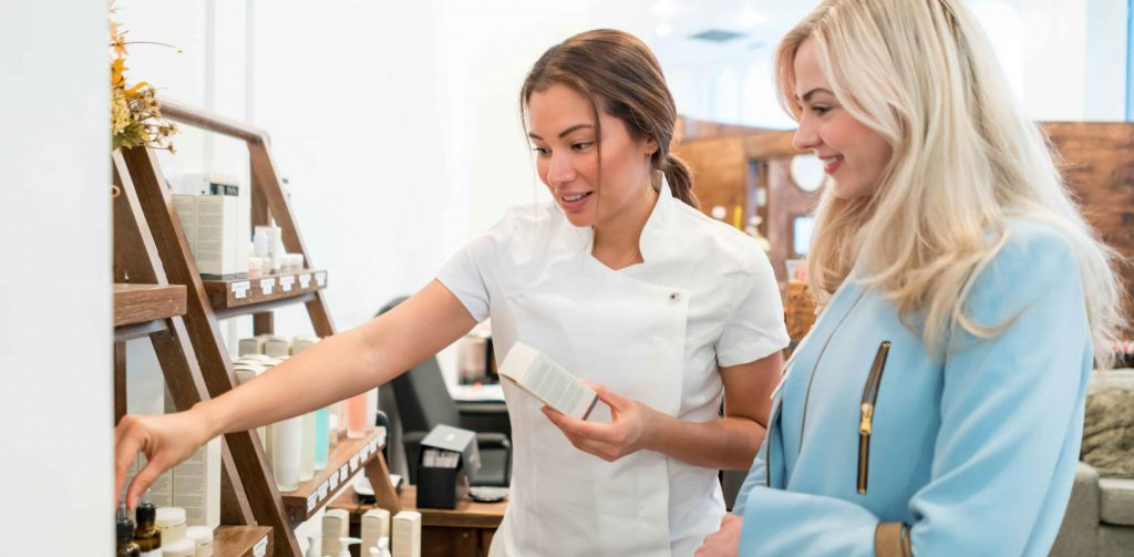 Sales employee assisting the customer with skincare beauty products.